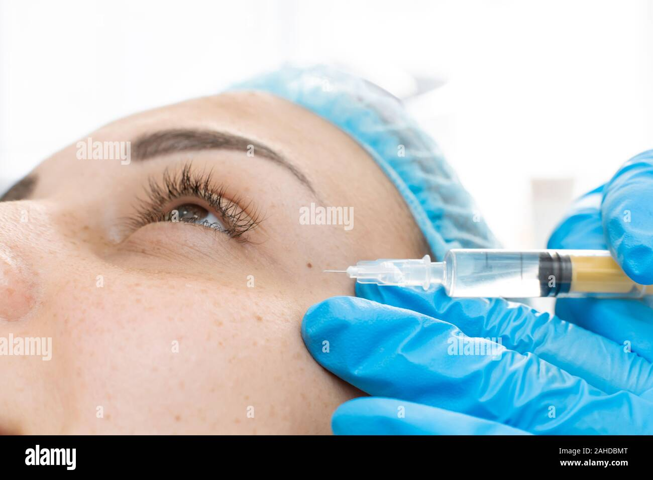 Close-up, beautician makes beauty injections into the skin of a young beautiful girl. Facial care and rejuvenation Stock Photo