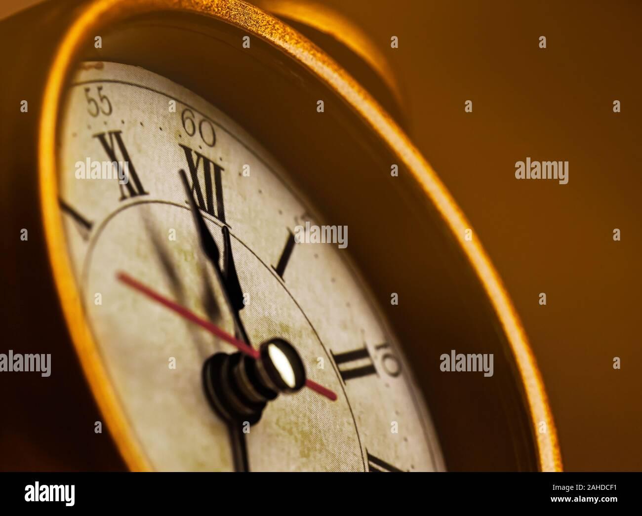 Golden vintage alarm clock showing five to twelve Stock Photo