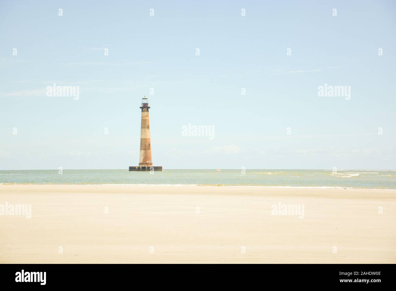 The iconic lighthouse, now on the National Register of Historic Places, rises above the seashore on Morris Island near Charleston, South Carolina. Stock Photo