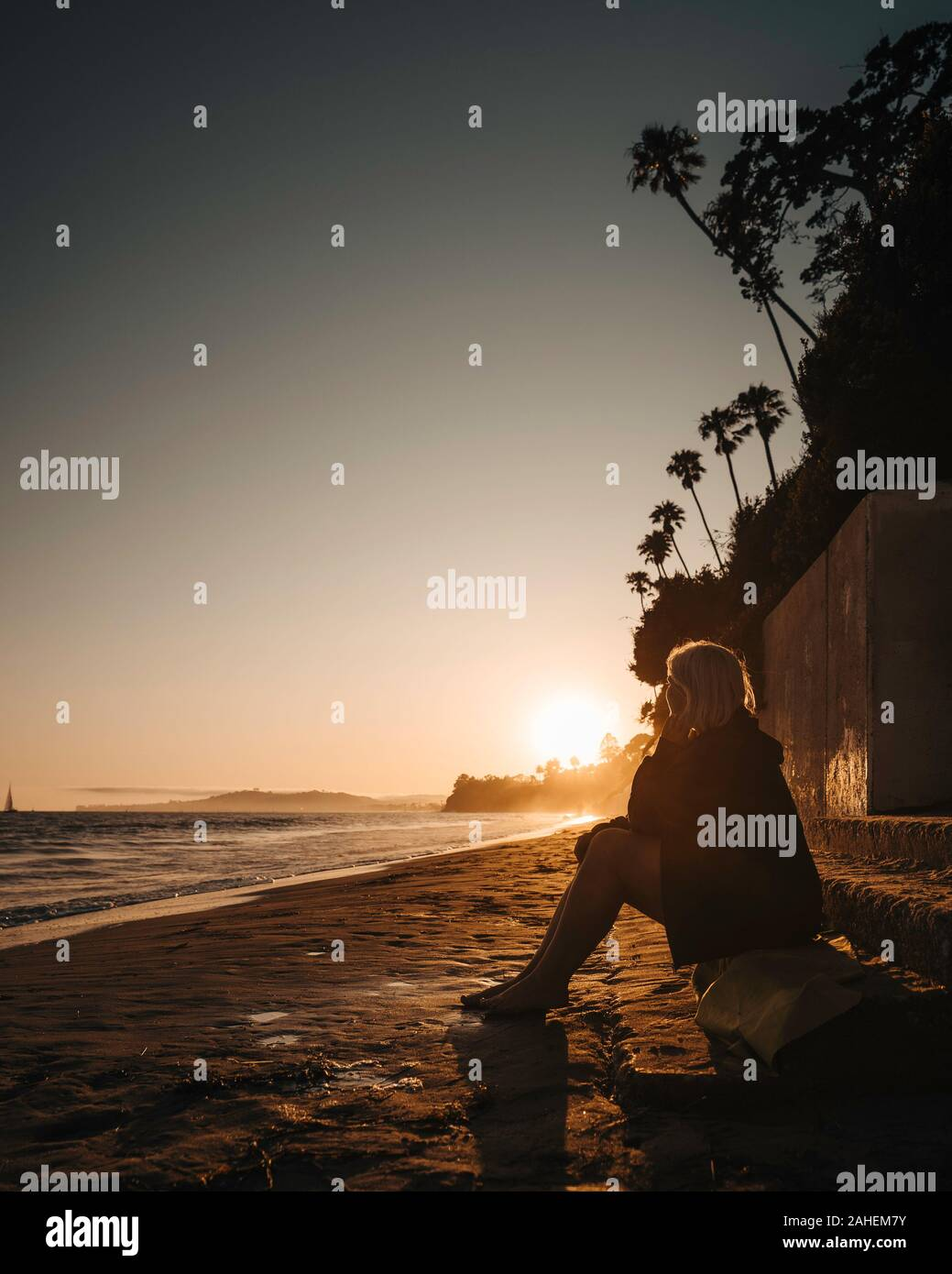 Women watches the sunset at the Beach Stock Photo