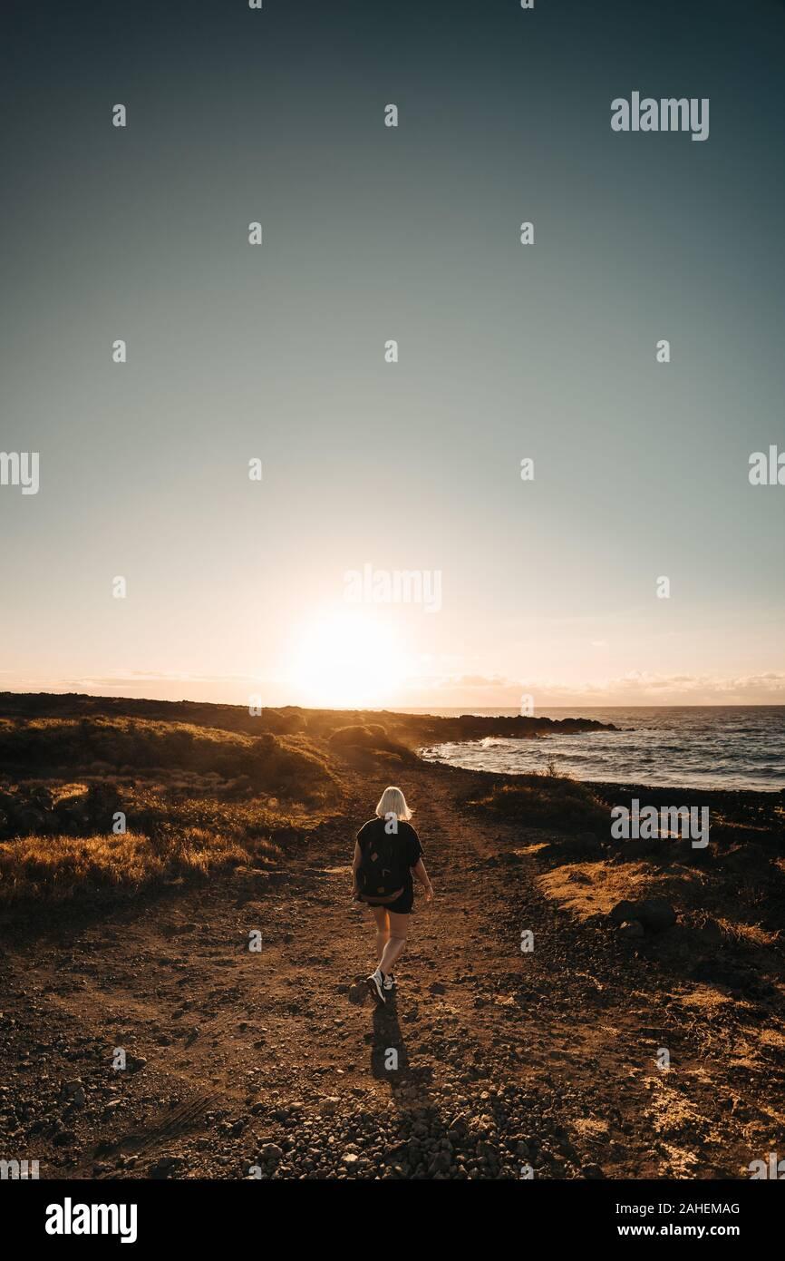 Women hikes during sunrise next to the Sea Stock Photo