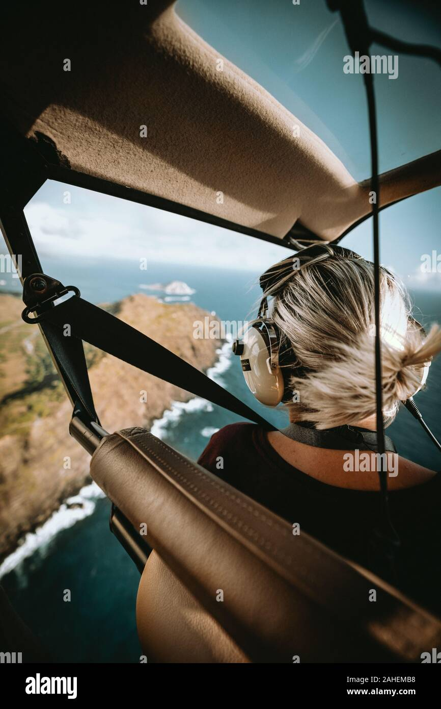 Open door helicopter flight with woman enjoying the view Stock Photo