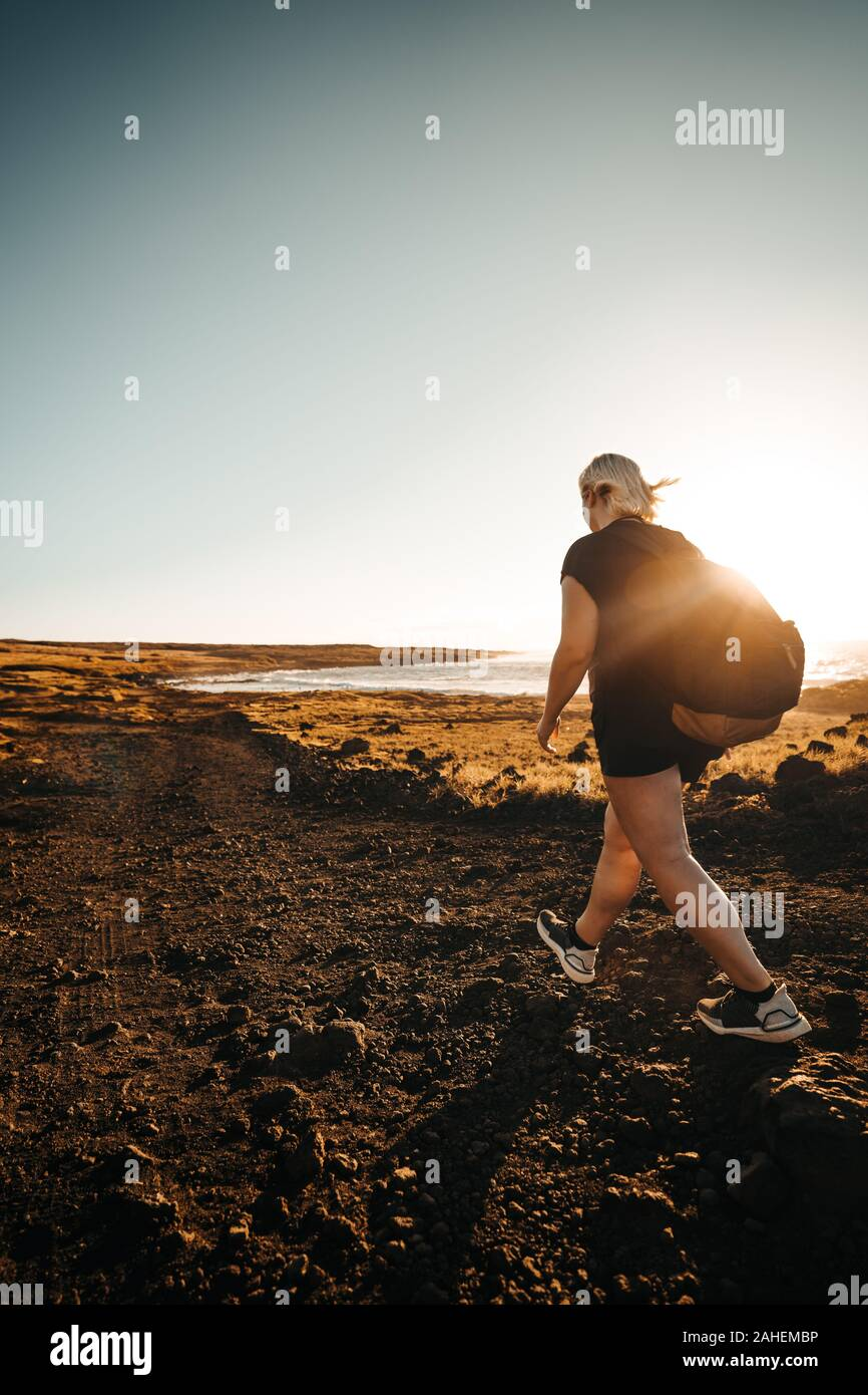 Women hikes during sunrise next to the Sea Stock Photo