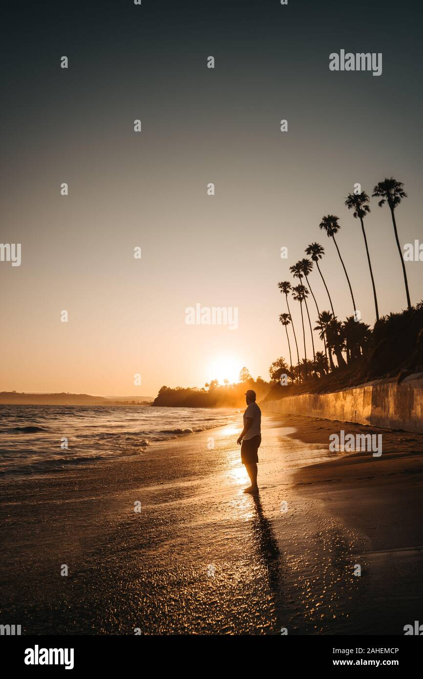 Men watches the sunset at the Beach Stock Photo
