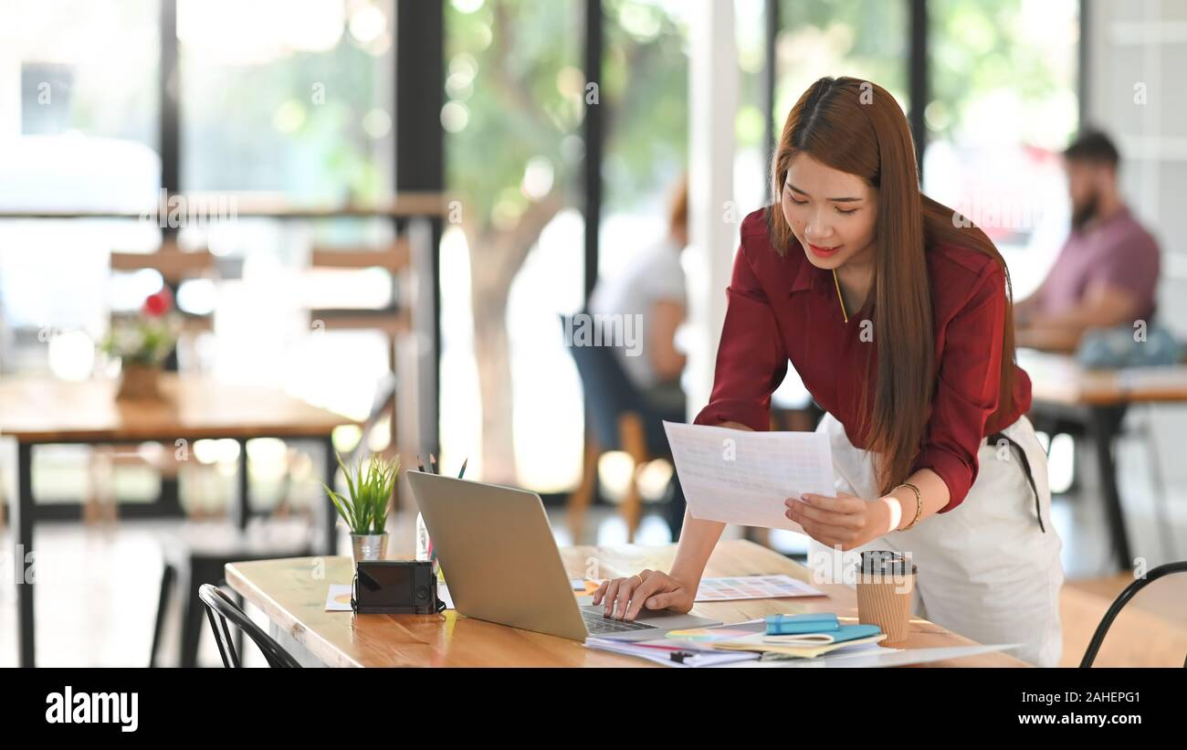 Young creative woman selected colour guide with laptop on artist work space. Stock Photo