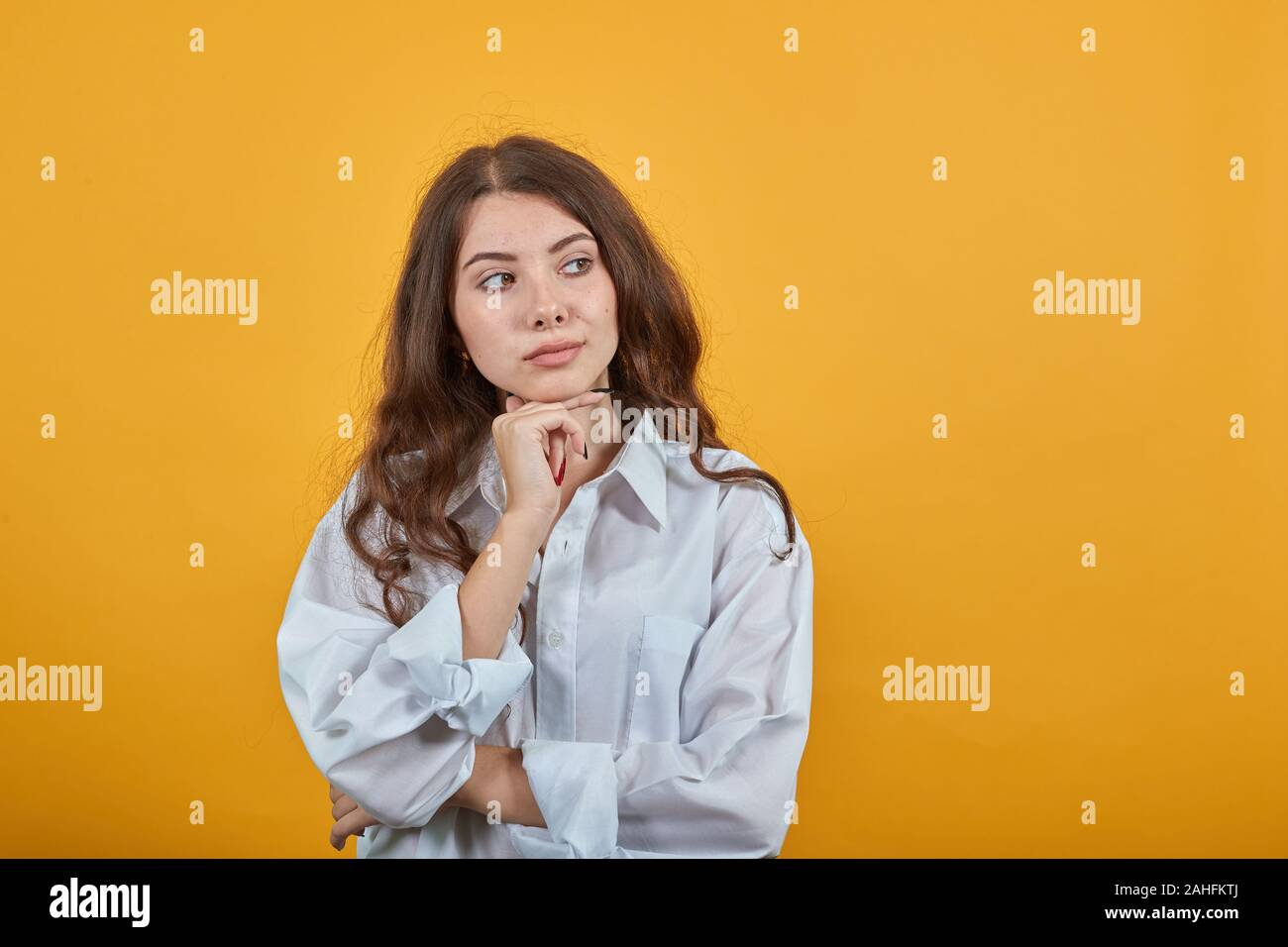 Focused young woman keeping hands on chin, looking aside, having nice haircut Stock Photo