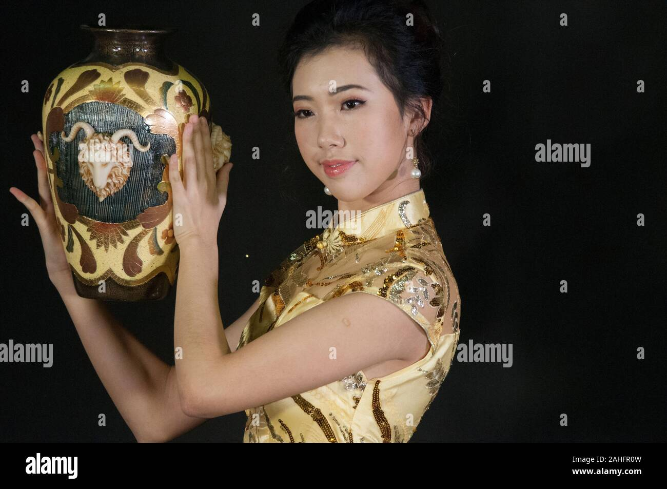 Head and shoulders of Asian female, wearing traditional Chinese qipao or cheongsam a traditional fashion Stock Photo