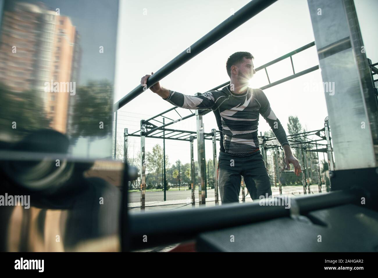 Calm sportsman putting hand on chin ups bar and turning his head Stock Photo