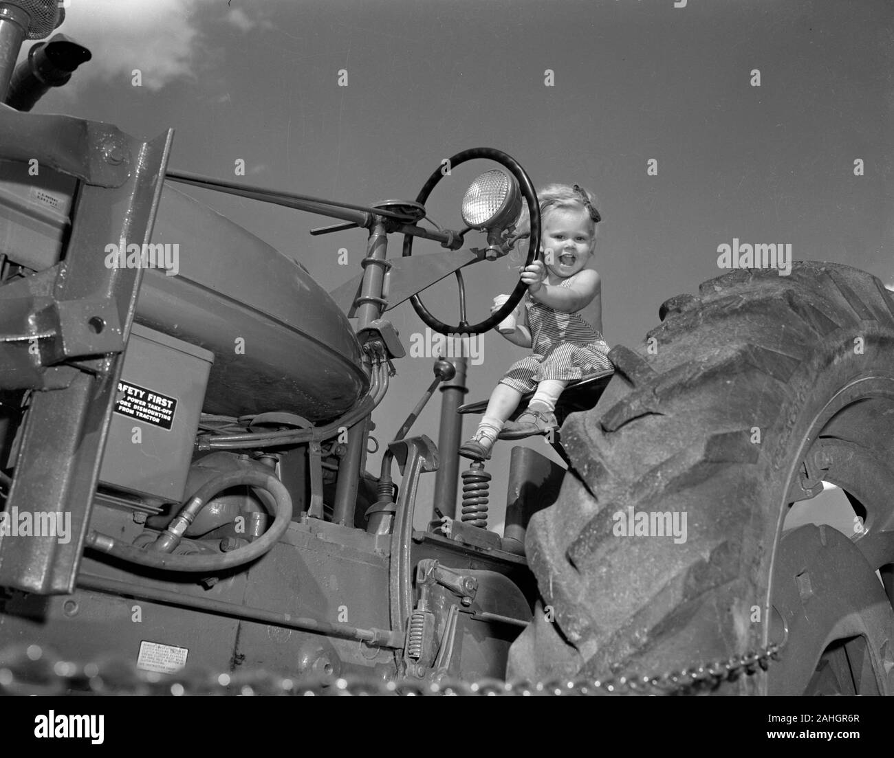 A girl sits on a tractor while eating ice cream, 1946 Stock Photo