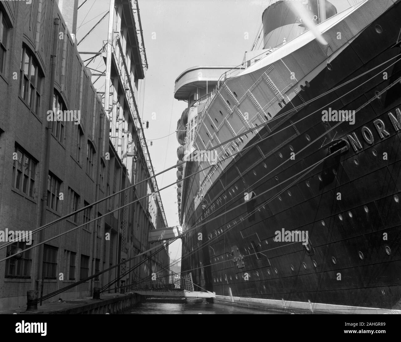 The SS Normandie, at dock in New York, during the process of being refitted to serve as a troop ship in WWII. The date of the photograph is uncertain, but it is clearly prior to the fire that beset the ship in February 1942 Stock Photo