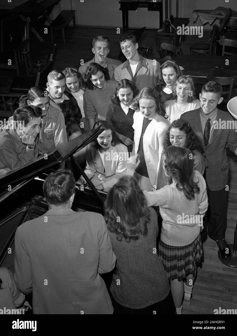 College students singing ith a piano player, 1945 Stock Photo