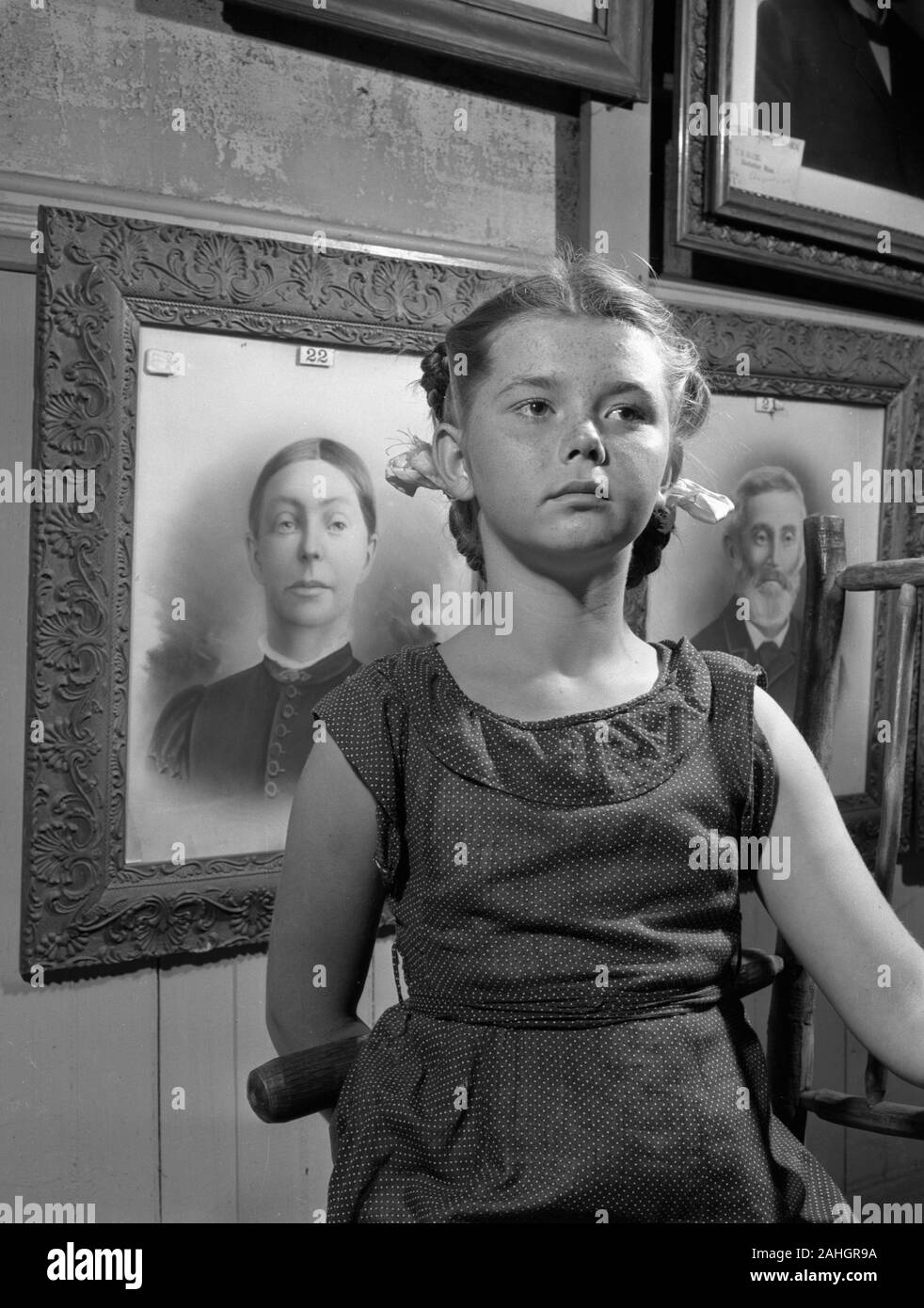 Girl standing in front of portraits of family members, 1946. This was part of the Minnesota State Fair in 1946, where people stood in front of portraits of their grandparents to illustrate genealogical traits. Stock Photo