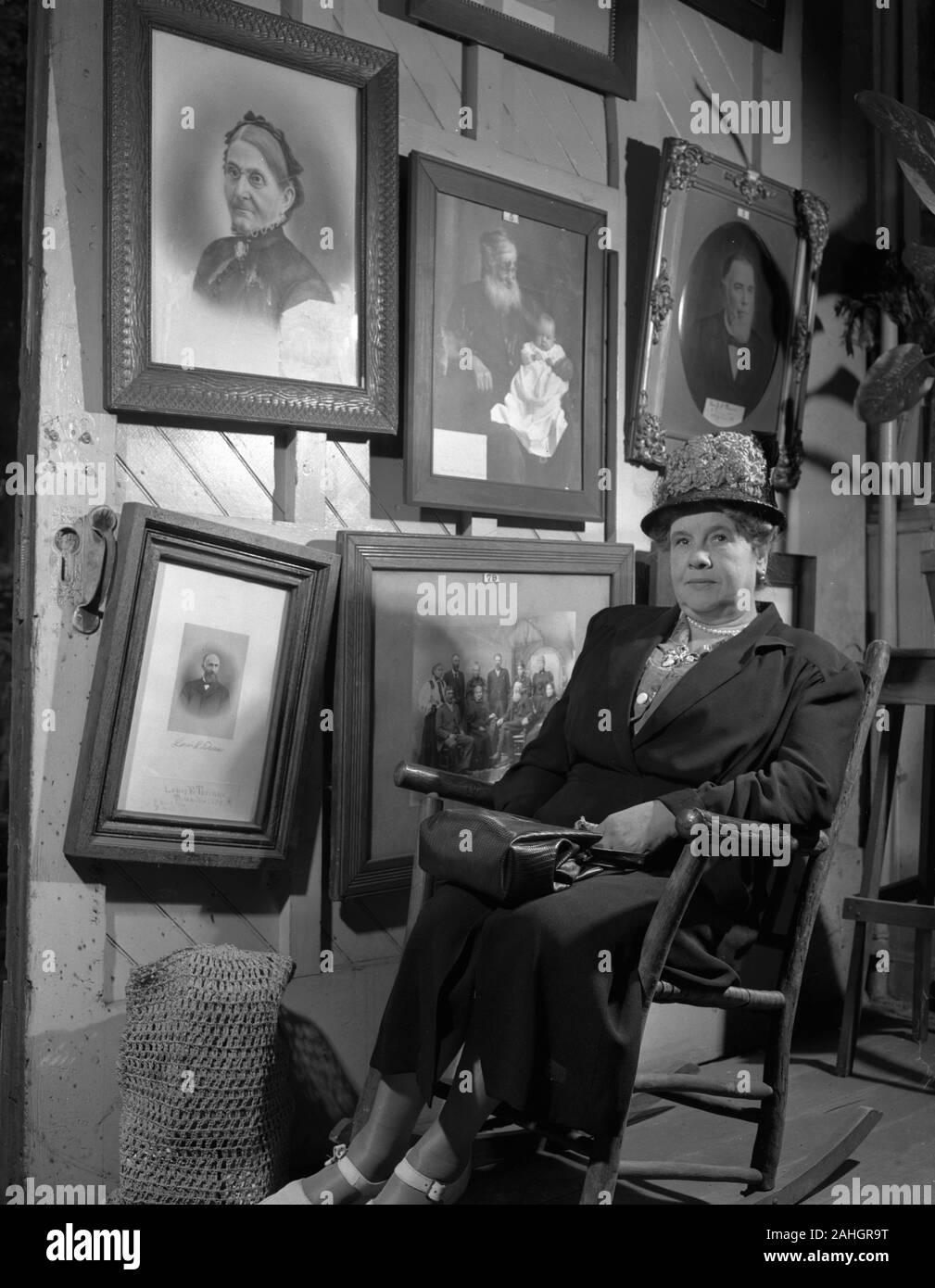 Woman seated in front of portraits of family members, 1946. This was part of the Minnesota State Fair in 1946, where people stood in front of portraits of their grandparents to illustrate genealogical traits. One of the portraits bears the name Louis E. Torinus Stock Photo