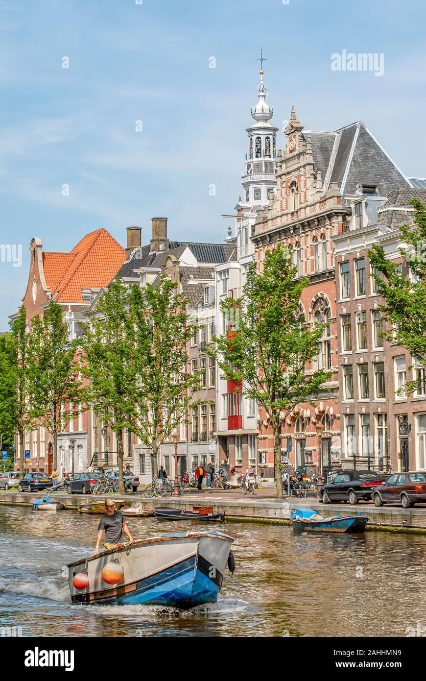 Small Boat running through a Amsterdam Water Channel, Netherlande Stock Photo