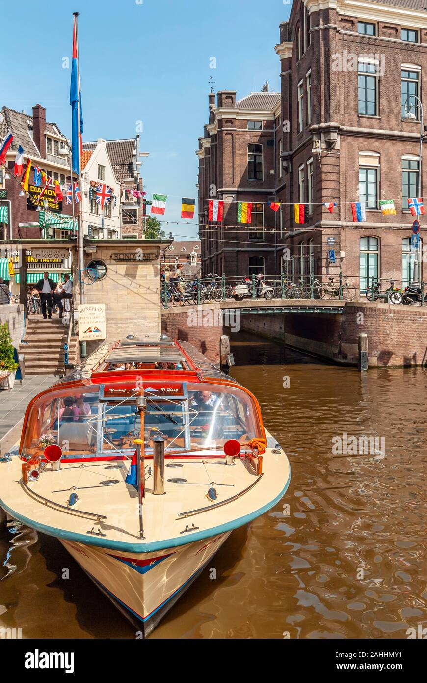 Typical sightseeing boats in a water channel in the city center of Amsterdam, Netherlands Stock Photo