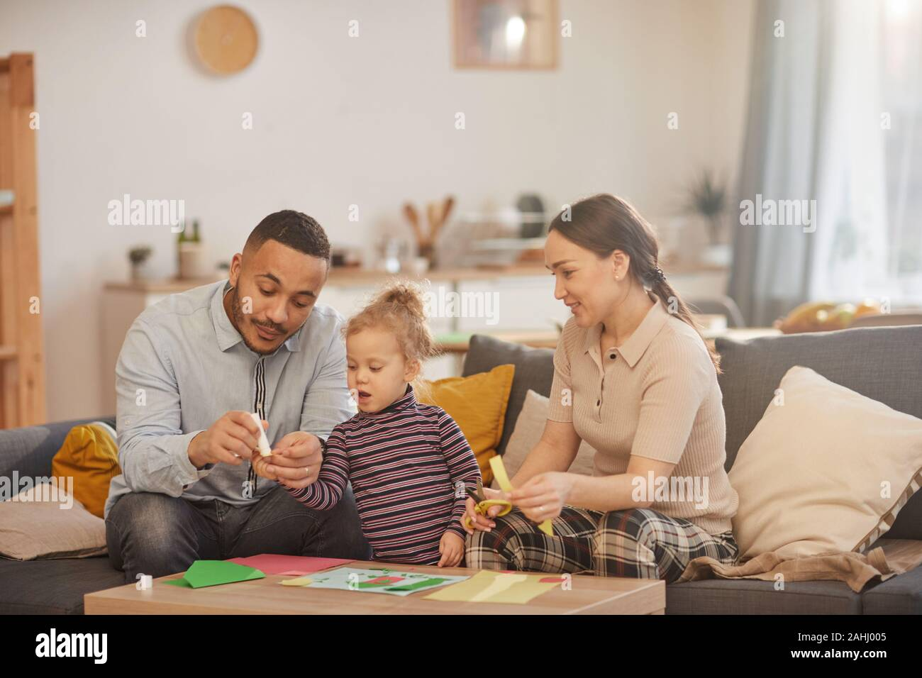 Warm toned portrait of happy mixed-race family playing with cute little daughter in cozy home interior Stock Photo