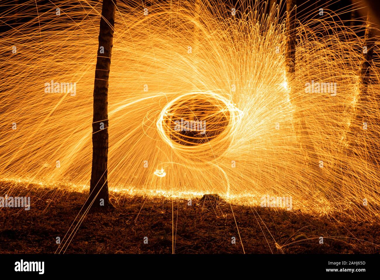 Fire circle spinning from steel wool creating spiral spark, Steel wool spinning fire circle spinning from steel wool creating spiral spark, birch grov Stock Photo