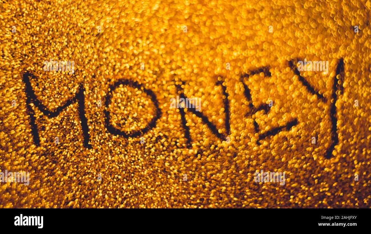 Text money on golden rich sandy background. Stock Photo