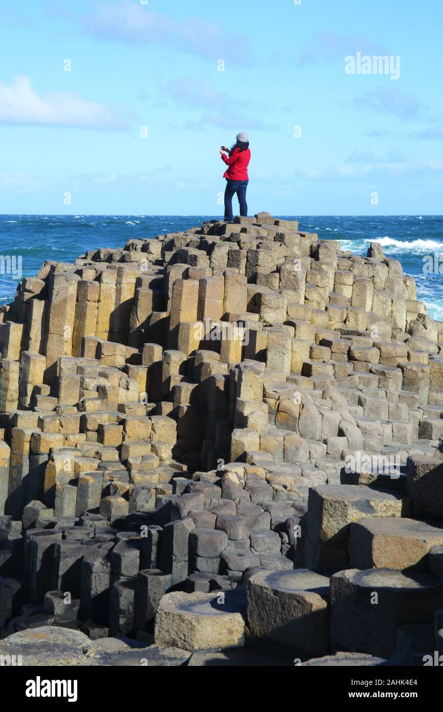 Massive basalt columns of the Giant's Causeway with woman in red jacket standing on the summit taking photographs with her mobile phone, blue sky and Stock Photo