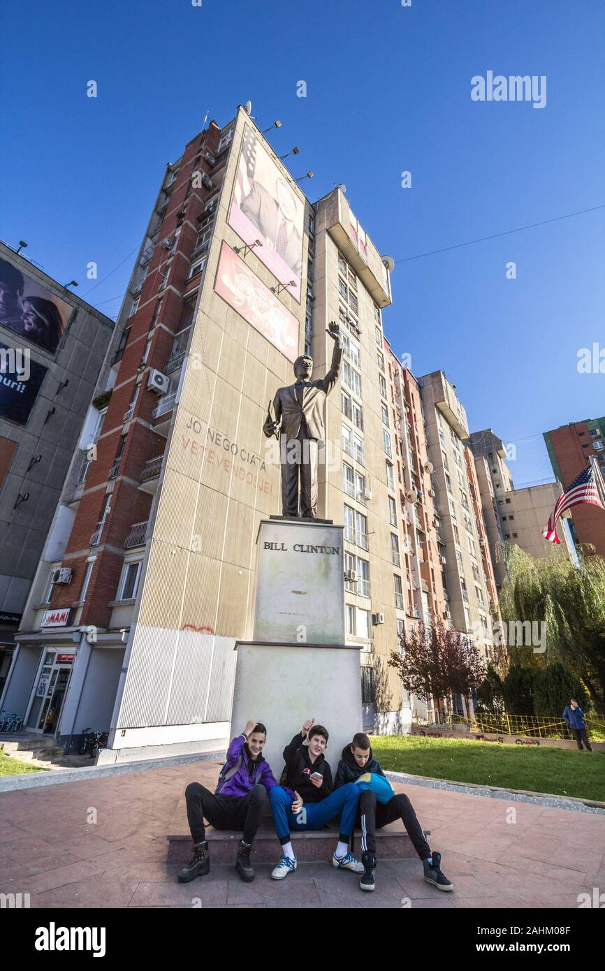PRISHTINA, KOSOVO - NOVEMBER 11, 2016: Bill Clinton Statue on Bill Klinton boulevard with Kosovan youngsters sitting down in front. The statue was ere Stock Photo