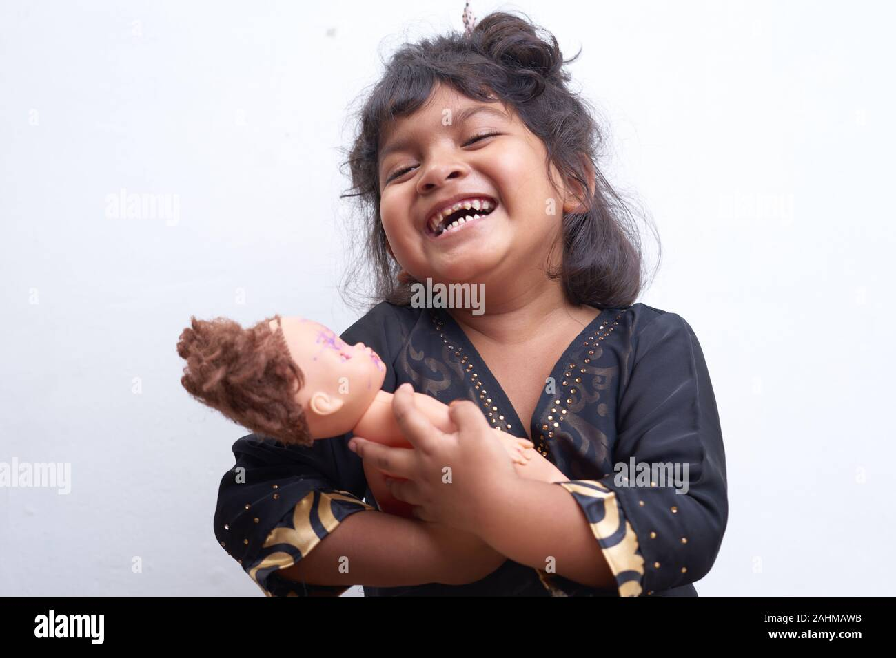 Asian little girl as a mom playing with a baby doll on white background Stock Photo