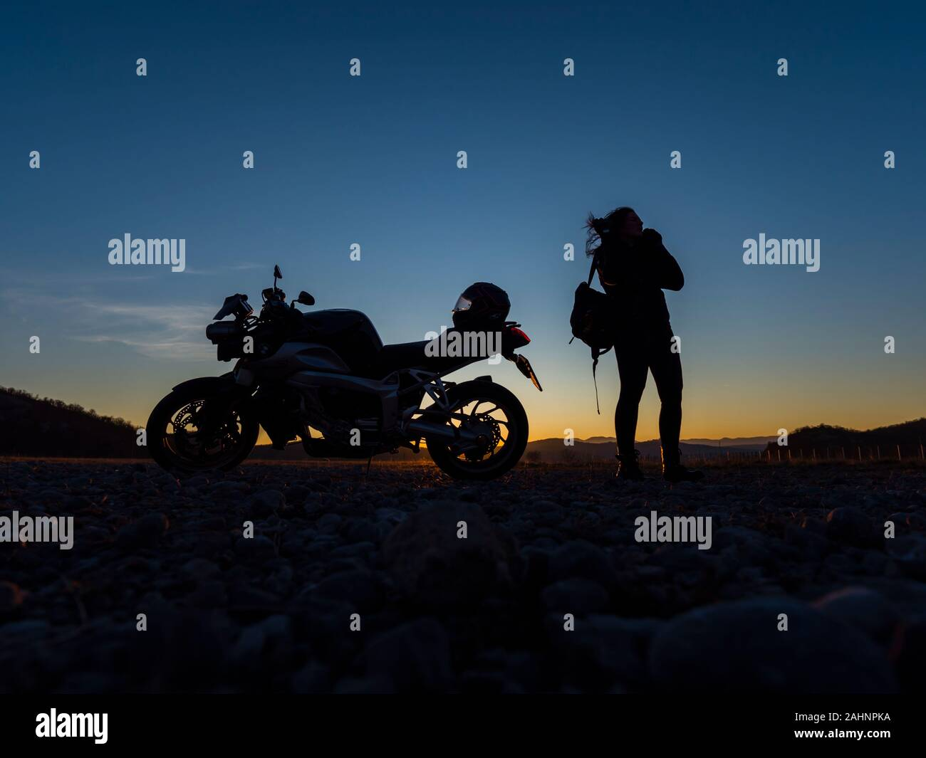 Sunset scenery scenic female motorcycle driver stretching her legs standing besides next to vehicle holding hold traveling rucksack Stock Photo