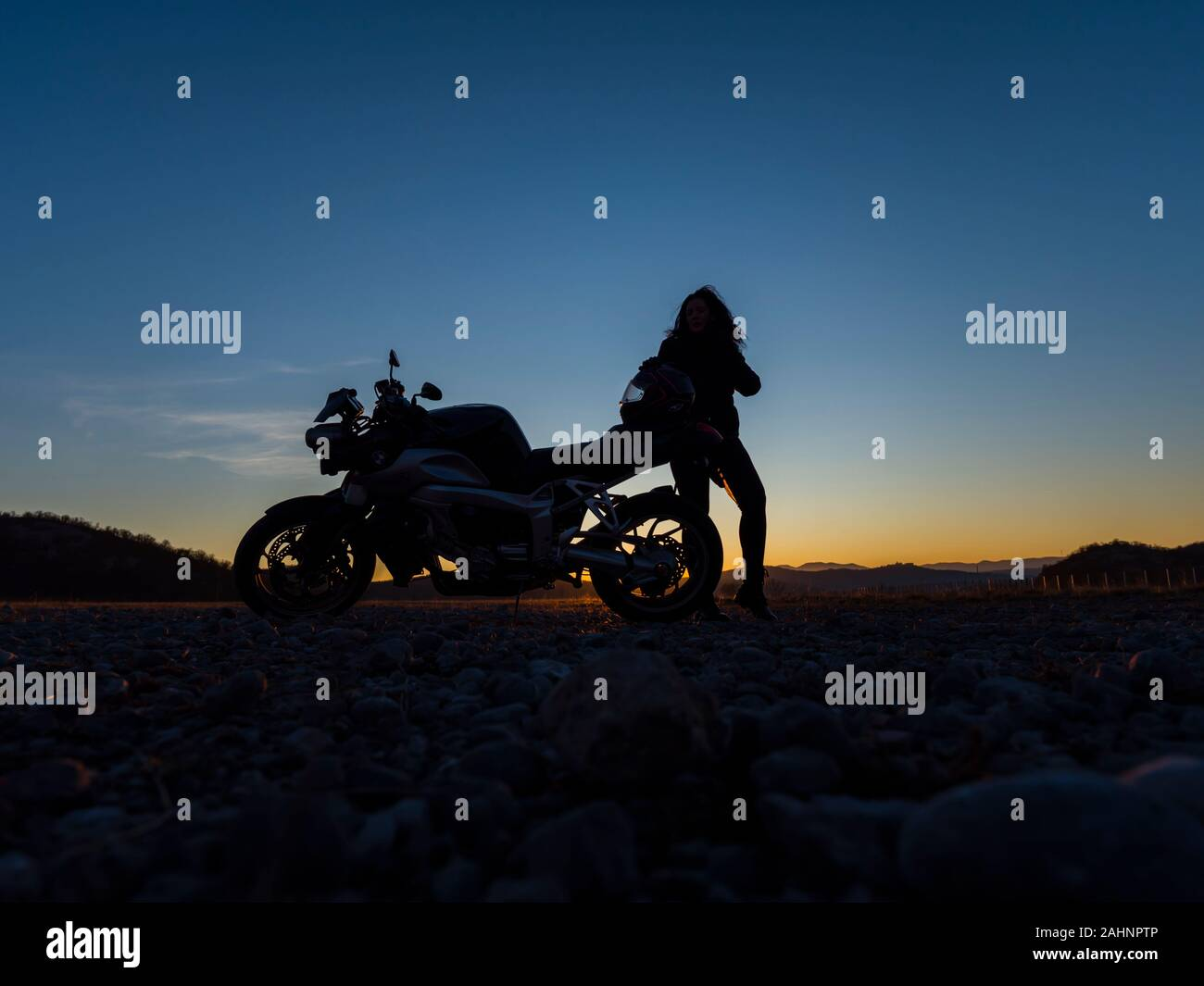 Sunset scenery scenic female motorcycle driver stretching her legs standing besides next to behind vehicle Stock Photo