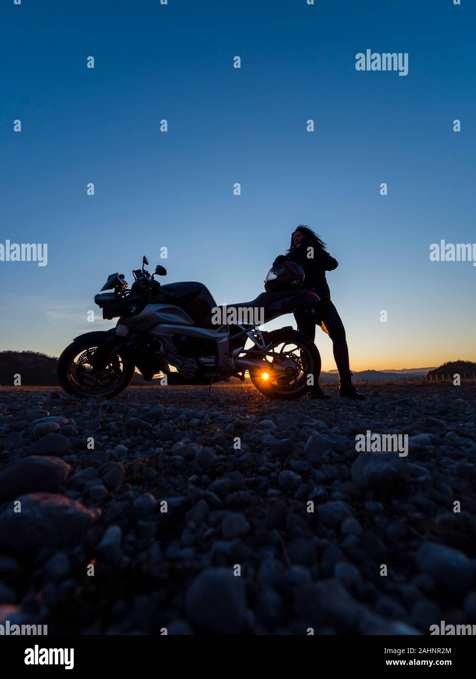 Sunset scenery scenic female motorcycle driver stretching her legs standing besides next to behind vehicle setting sun peek Stock Photo