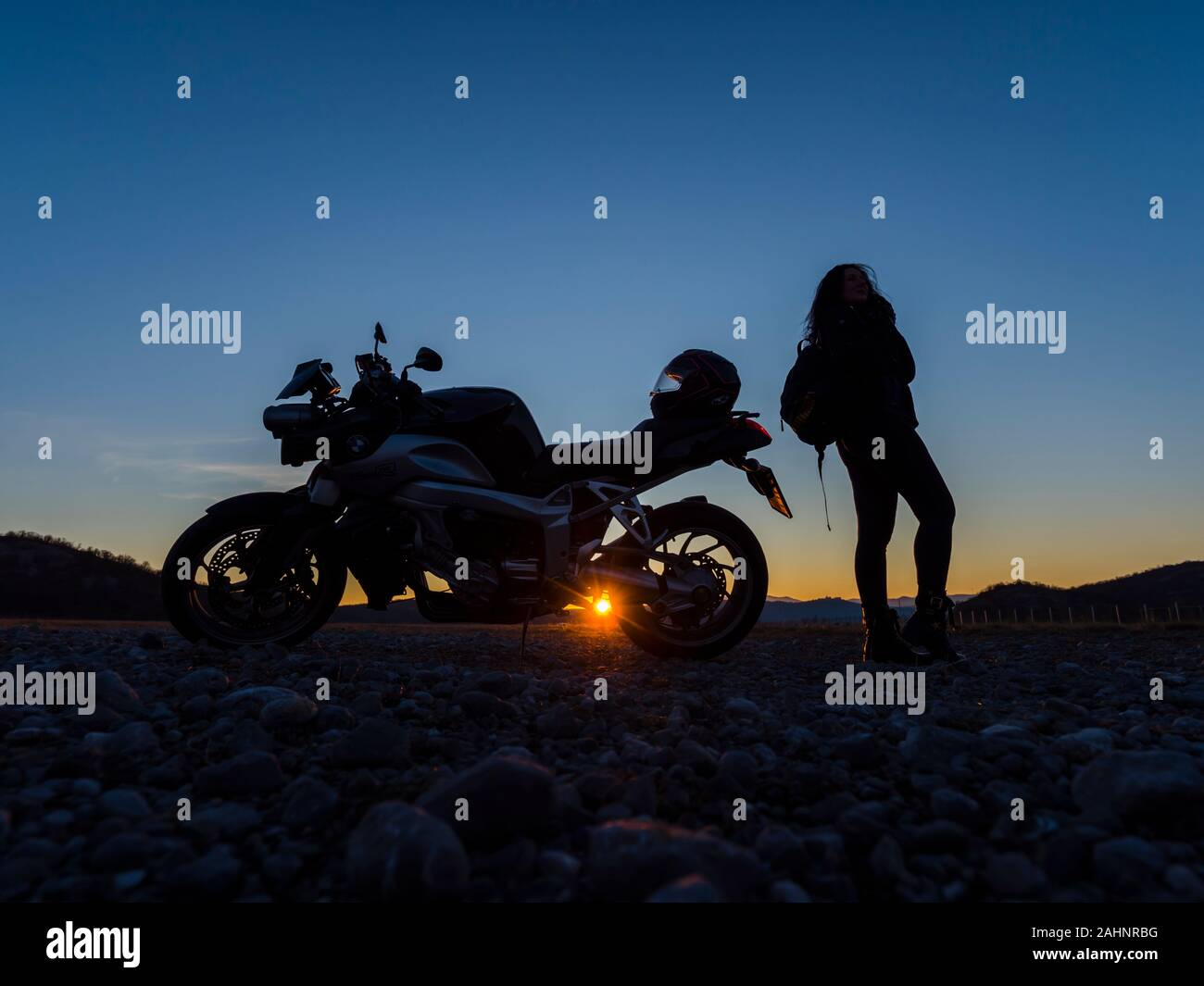 Sunset scenery scenic female motorcycle driver stretching her legs standing besides next to vehicle holding hold traveling rucksack setting sun peek Stock Photo