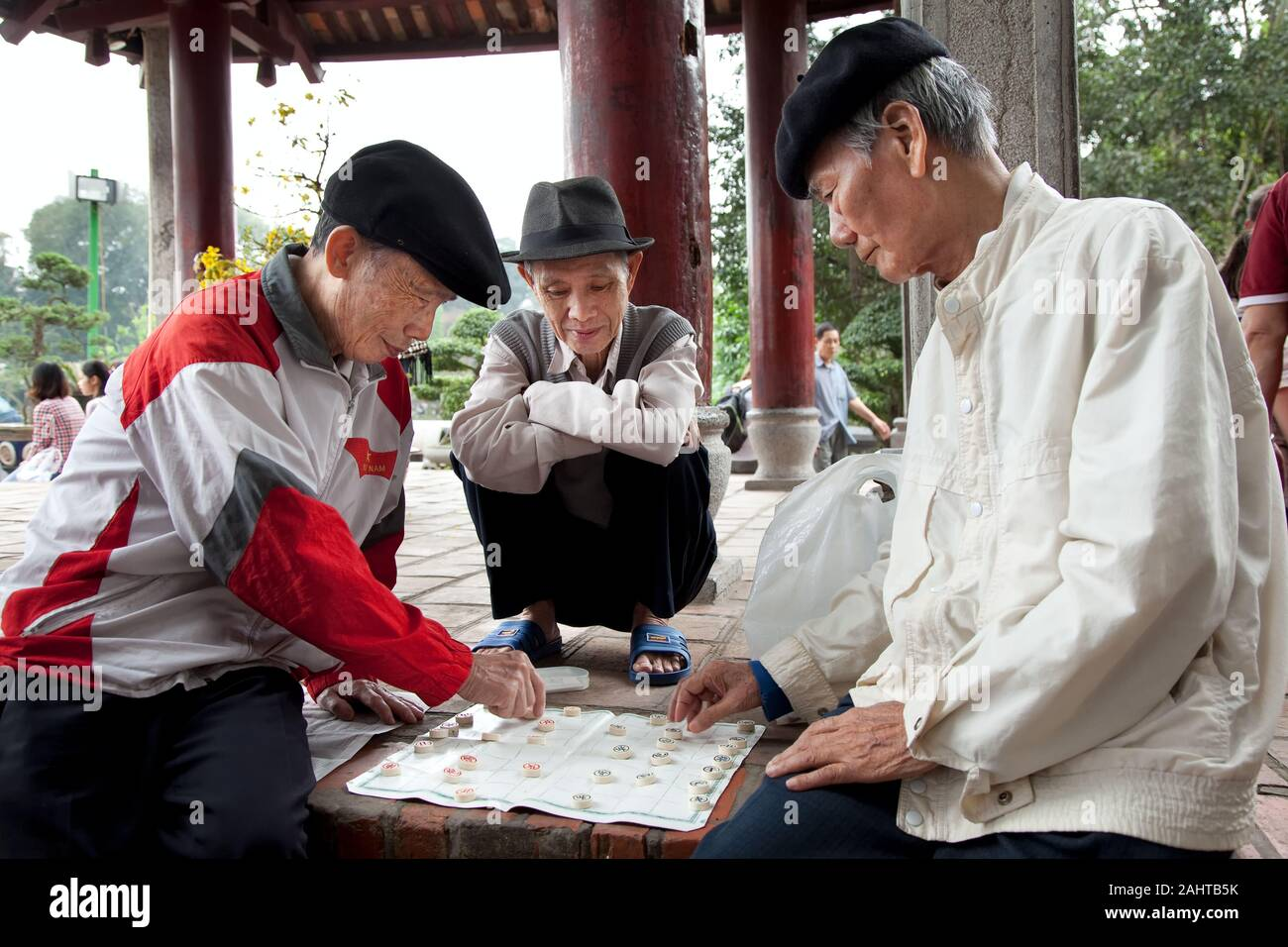 3 elderly people play a board game outside under a canopy and have a lot of fun, Hanoi Vietnam Stock Photo