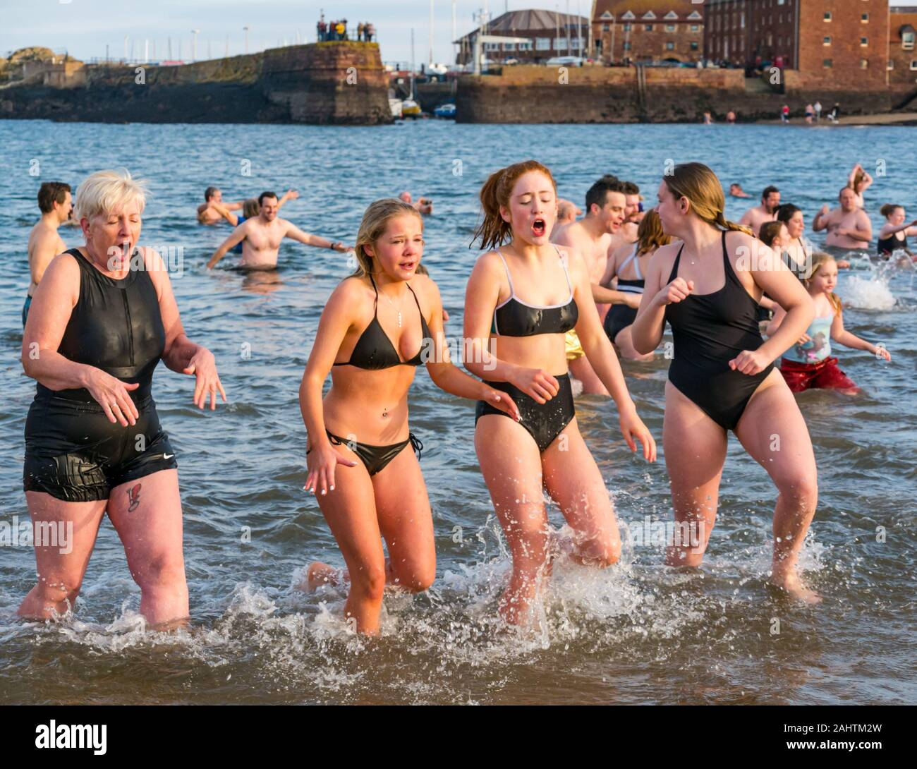 North Berwick, East Lothian, United Kingdom, 01 January 2020. Loony Dook: Hundreds of people brave the chilly water of the Firth of Forth to welcome 2020 in a Scottish New Year tradition, or New Year's Dip. A group of young women wearing bikinis and an older woman come out of the sea feeling very cold Stock Photo