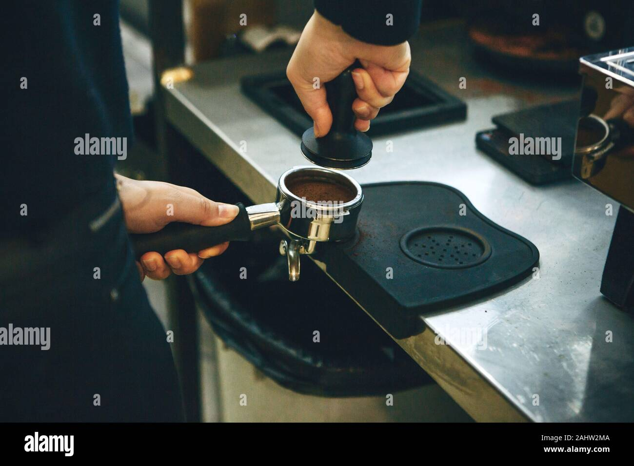 Barista presses ground coffee using tamper. Close-up view on hands with portafilter Stock Photo
