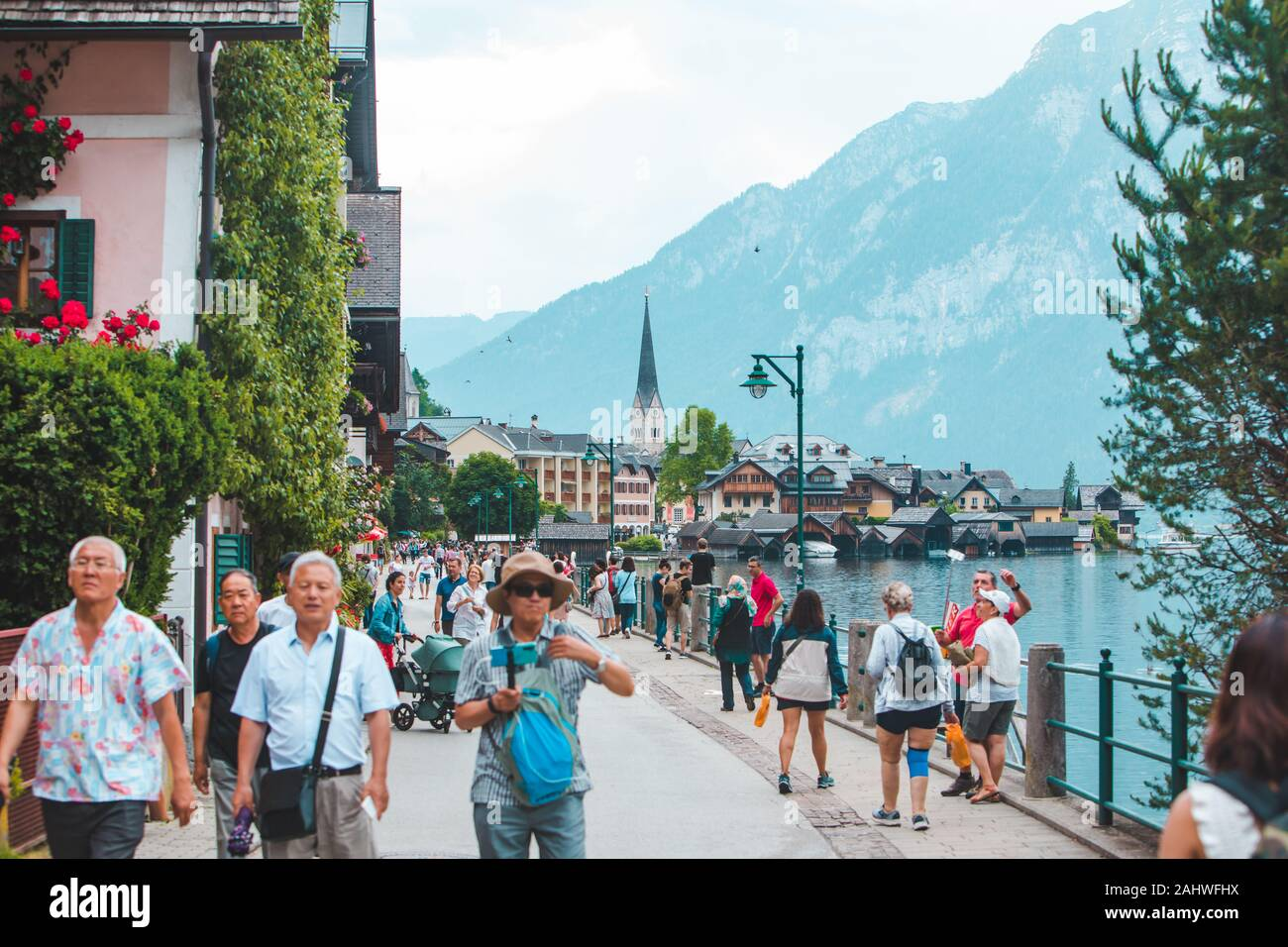 Hallstatt, Austria - June 15, 2019: people walking by city quay enjoying the view Stock Photo