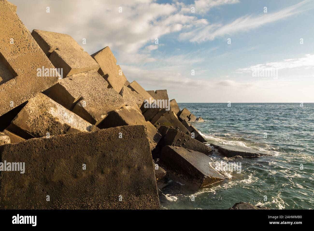 Breakwater blocks in the port of Puerto Rico, Gran Canaria, with the Atlantic Ocean in the background Stock Photo
