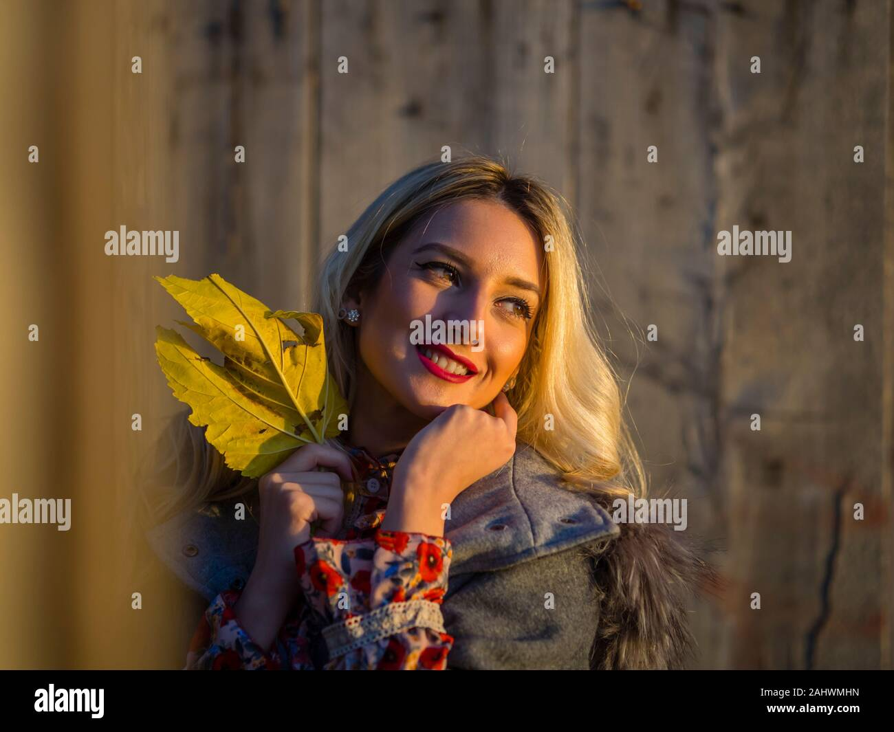 Portrait head and shoulders with Autumn leaf in hand looking away aside in distance setting sun sunset nature natural environment Stock Photo