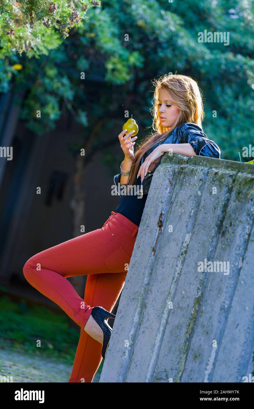 Eating hand holding hold pear fruit serious standing inclined on concrete wall serious looking down raised one leg up sideview side-view appetite Stock Photo