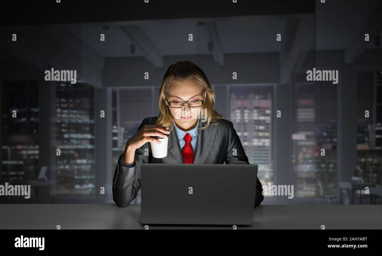 Businesswoman Sitting At Desk And Looking At Laptop Secretary In
