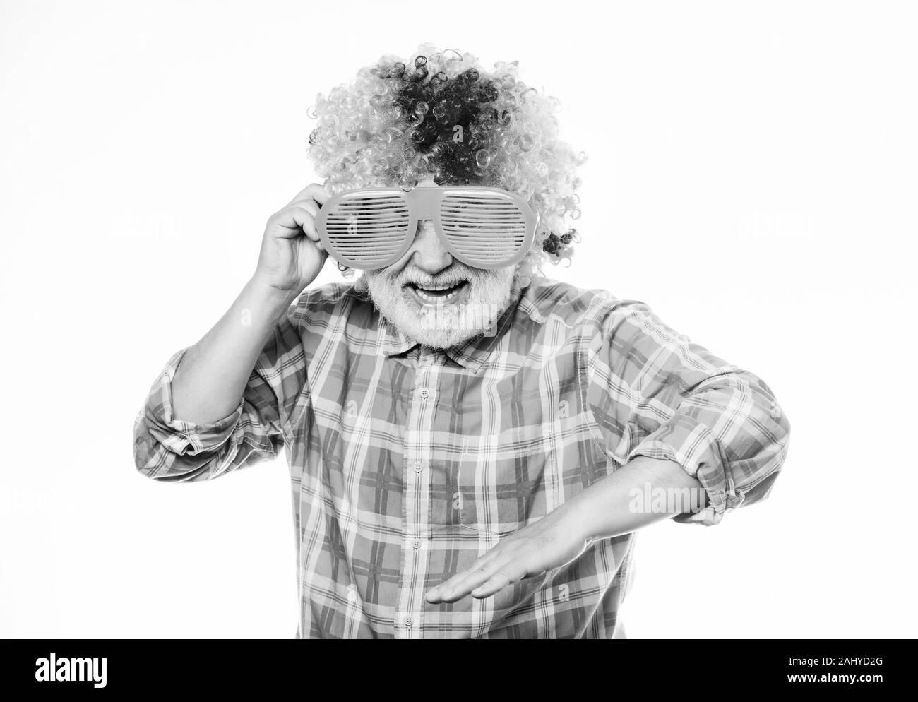 Nice joke. Grandpa always fun. Elderly clown. Man senior bearded cheerful person wear colorful wig and sunglasses. Having fun. Funny lifestyle. Fun and entertainment. Comic grandfather concept. Stock Photo