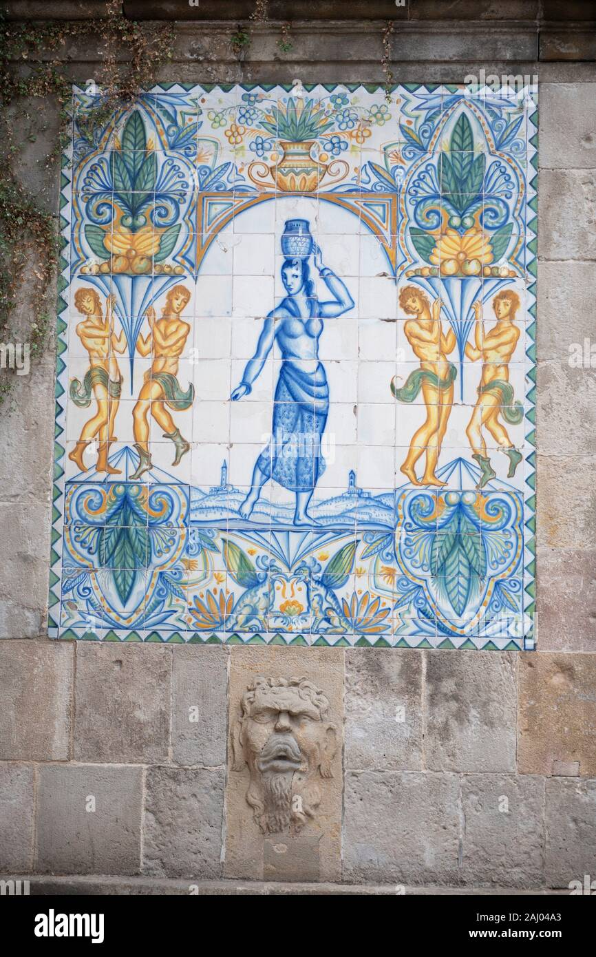 Ceramic tiles from 1918 of woman carrying water, Santa Ana fountain, Carrer del Cucurella, Portal de lâ.Angel, Gothic Quarter, Barcelona, Catalonia, Stock Photo