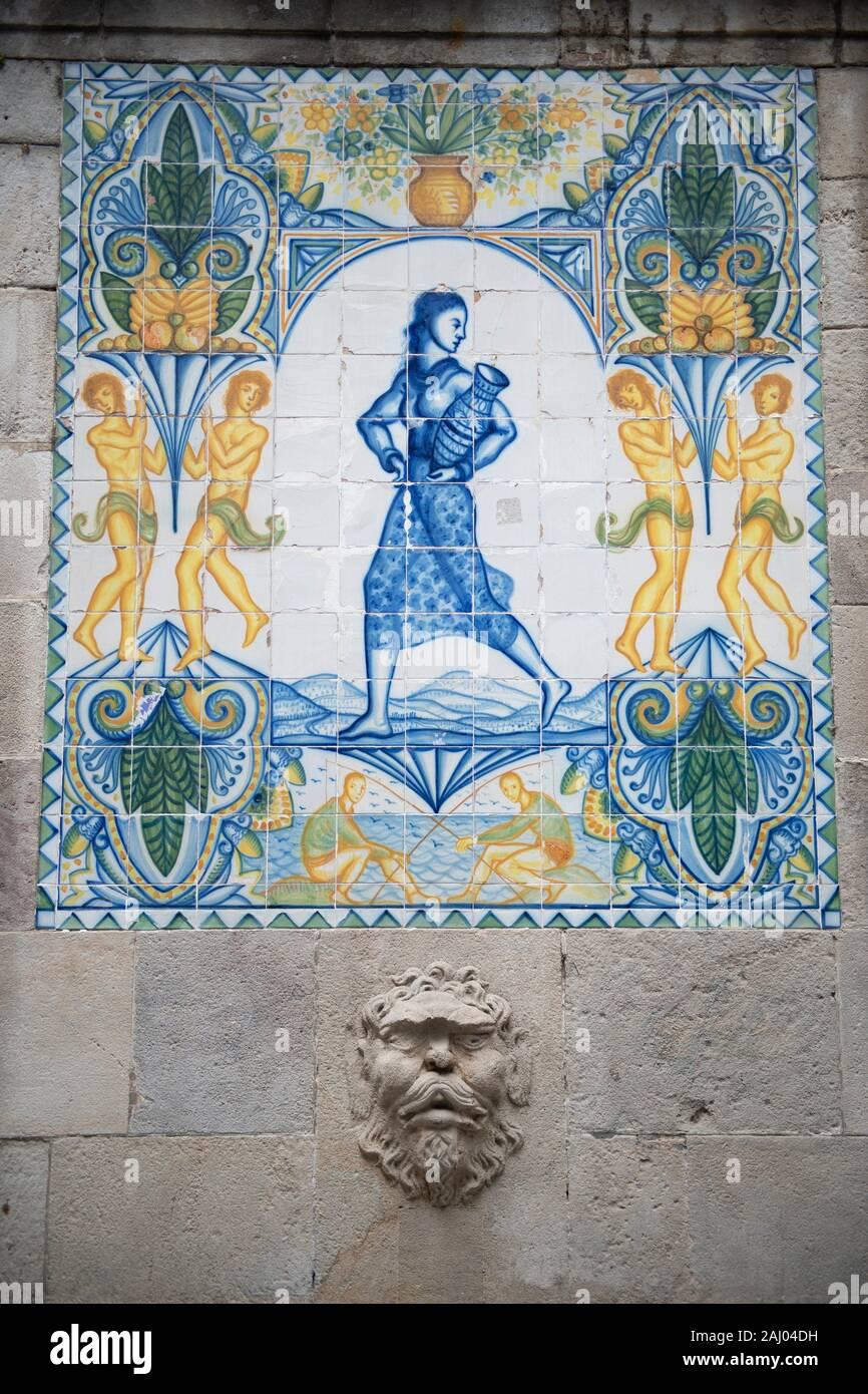 Ceramic tiles from 1918 of woman carrying water, Santa Ana fountain, Carrer del Cucurella, Portal de lâ.Angel, Gothic Quarter, Barcelona, Catalonia, Stock Photo