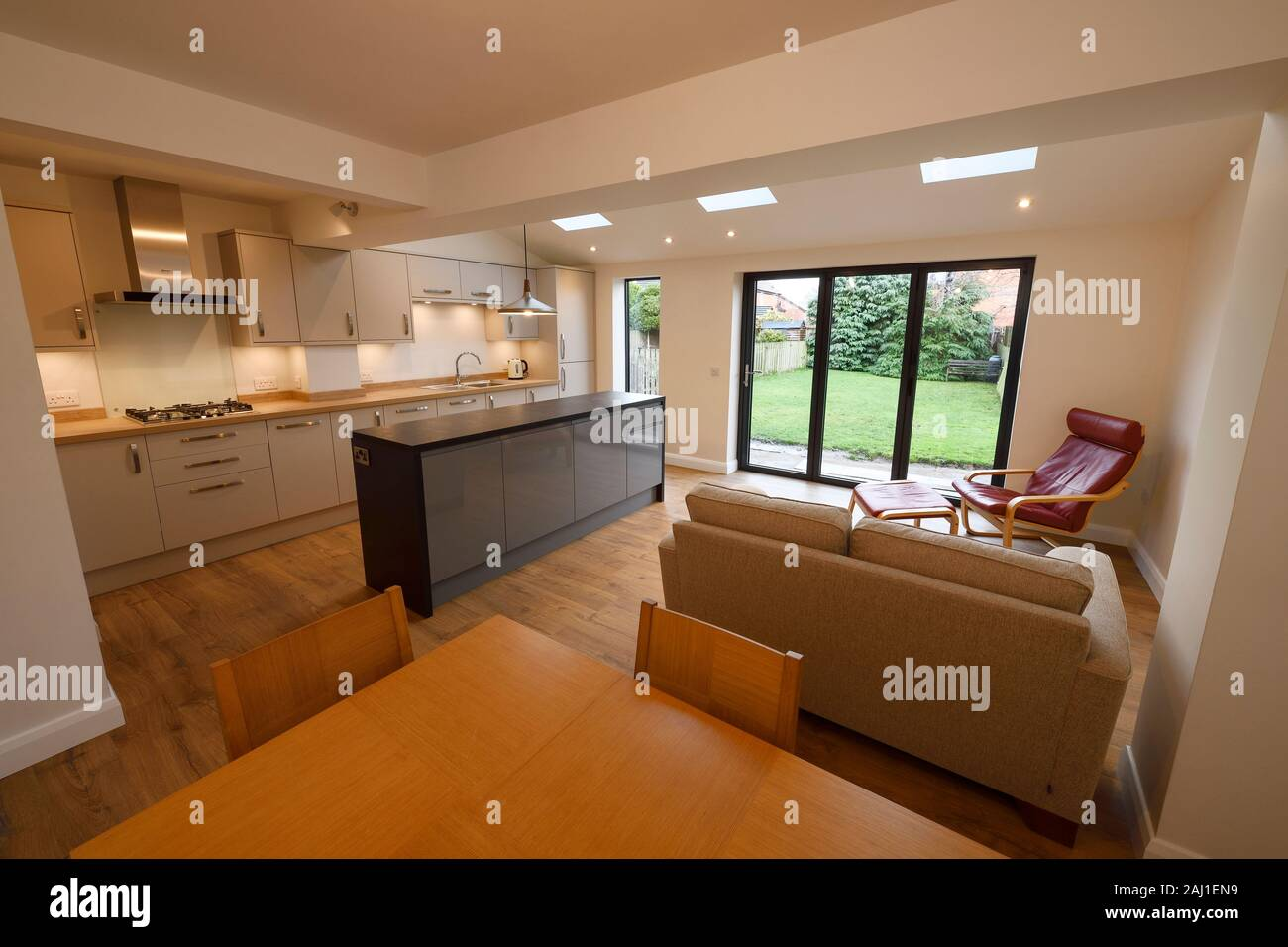 A modern open plan kitchen dining living room rear extension to a property in Chester with bifold doors and velds skylights Stock Photo