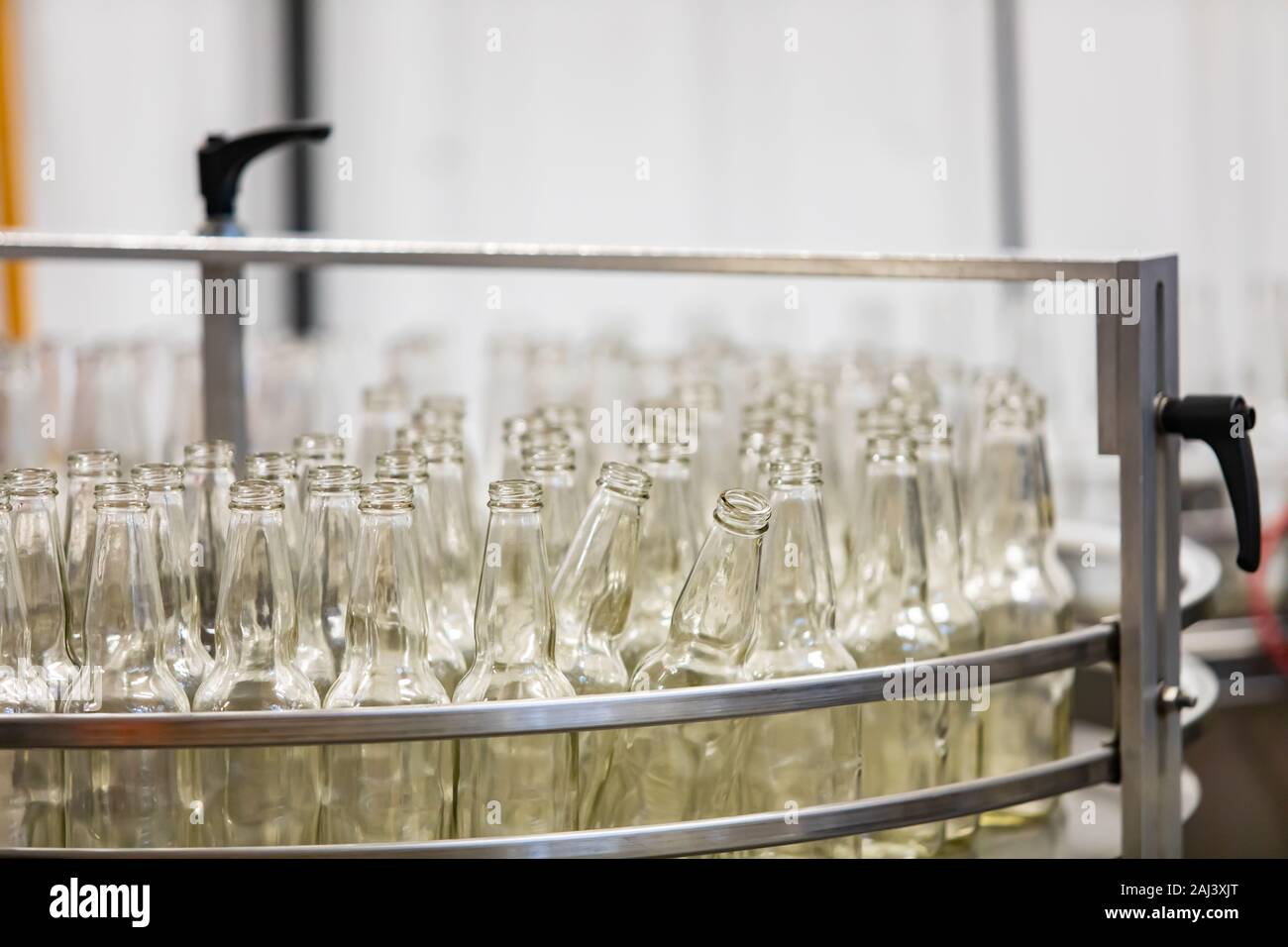 a lot of new white glass empty beer bottles on machine, selective focus close up view, conveyor belt craft brewery factory microbrewery Stock Photo