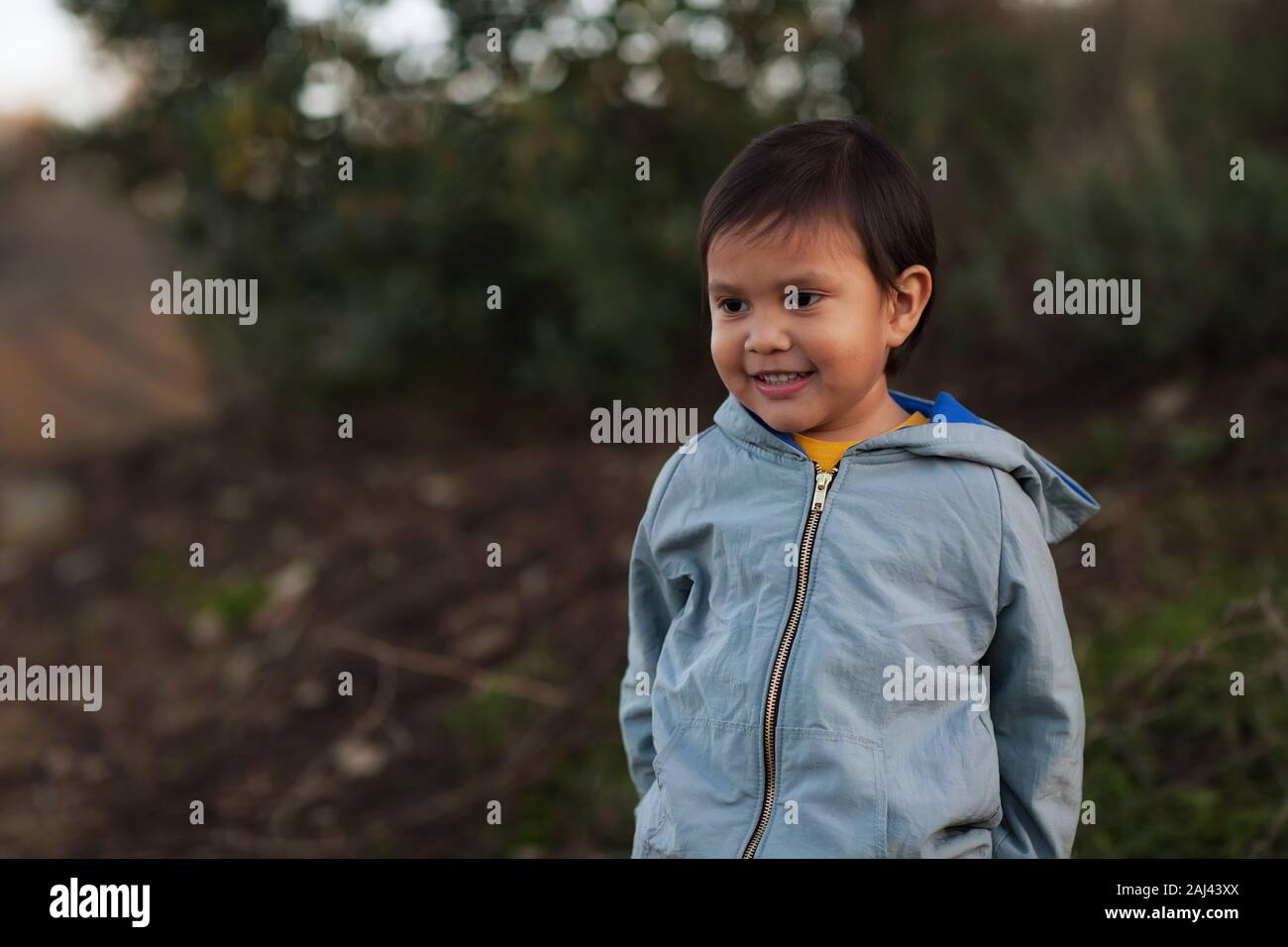 A hispanic young boy wearing a jacket and enjoying a day in the wilderness. Stock Photo
