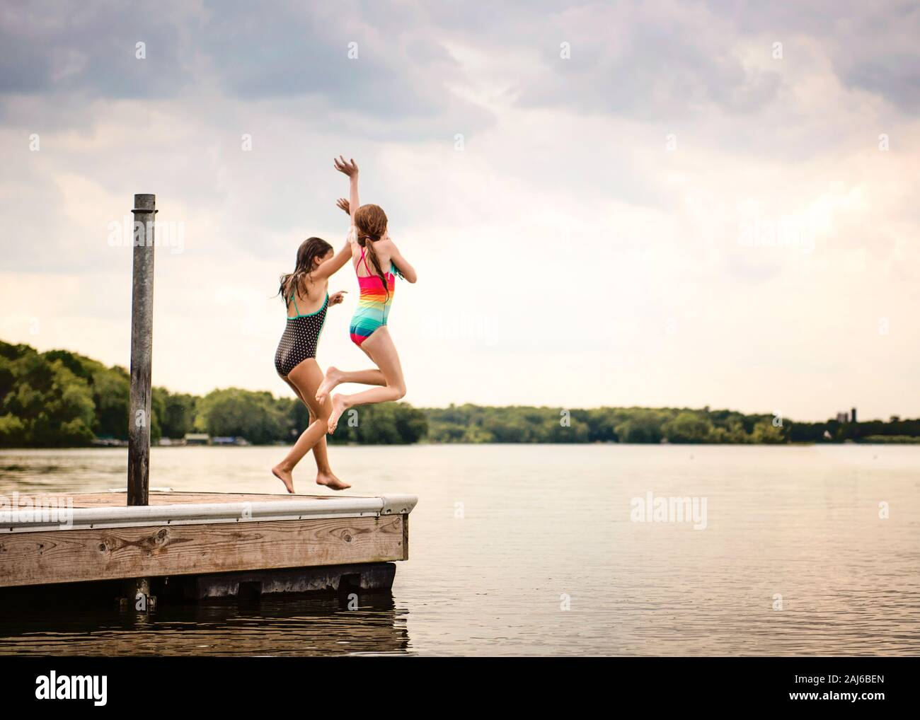 Two Young Girls in Swimsuits Jumping off a Dock into a Lake Stock Photo