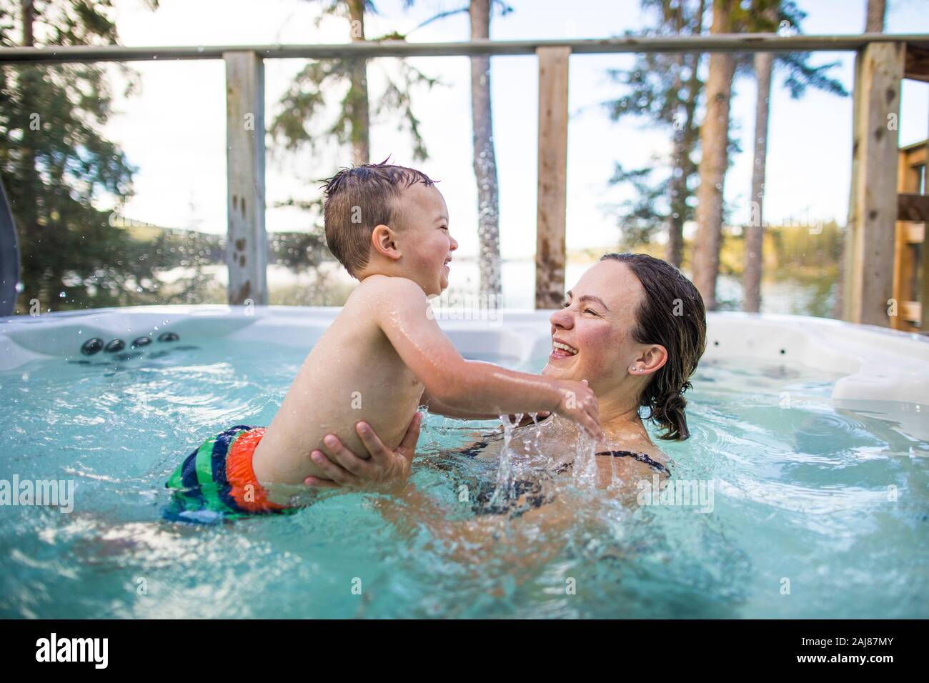 Young boy splashing and playing with mother in swimming pool Stock Photo