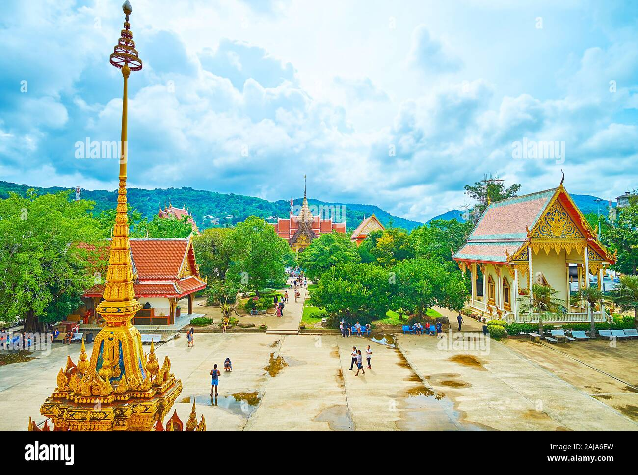 CHALONG, THAILAND - APRIL 30, 2019: The shrines on the grounds of Wat Chalong temple complex with a view on the spire and finial of the chedi on the f Stock Photo