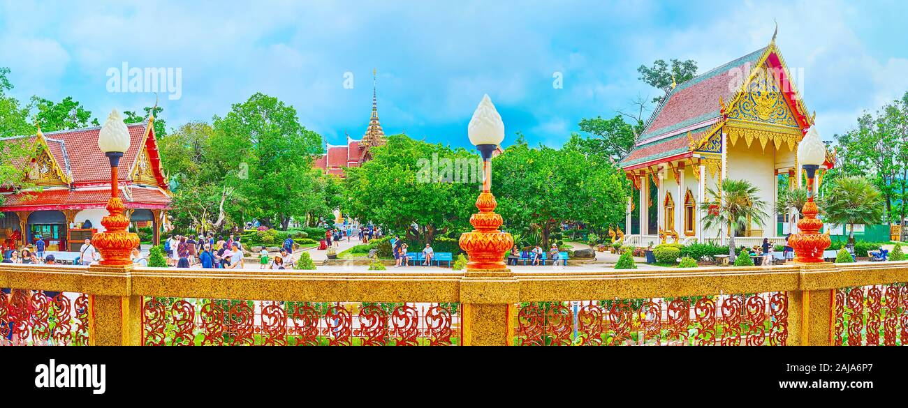 CHALONG, THAILAND - APRIL 30, 2019: Panorama of Wat Chaiyathararam (Wat Chalong) temple with ornate shrines, shady green garden and lace-like fence on Stock Photo