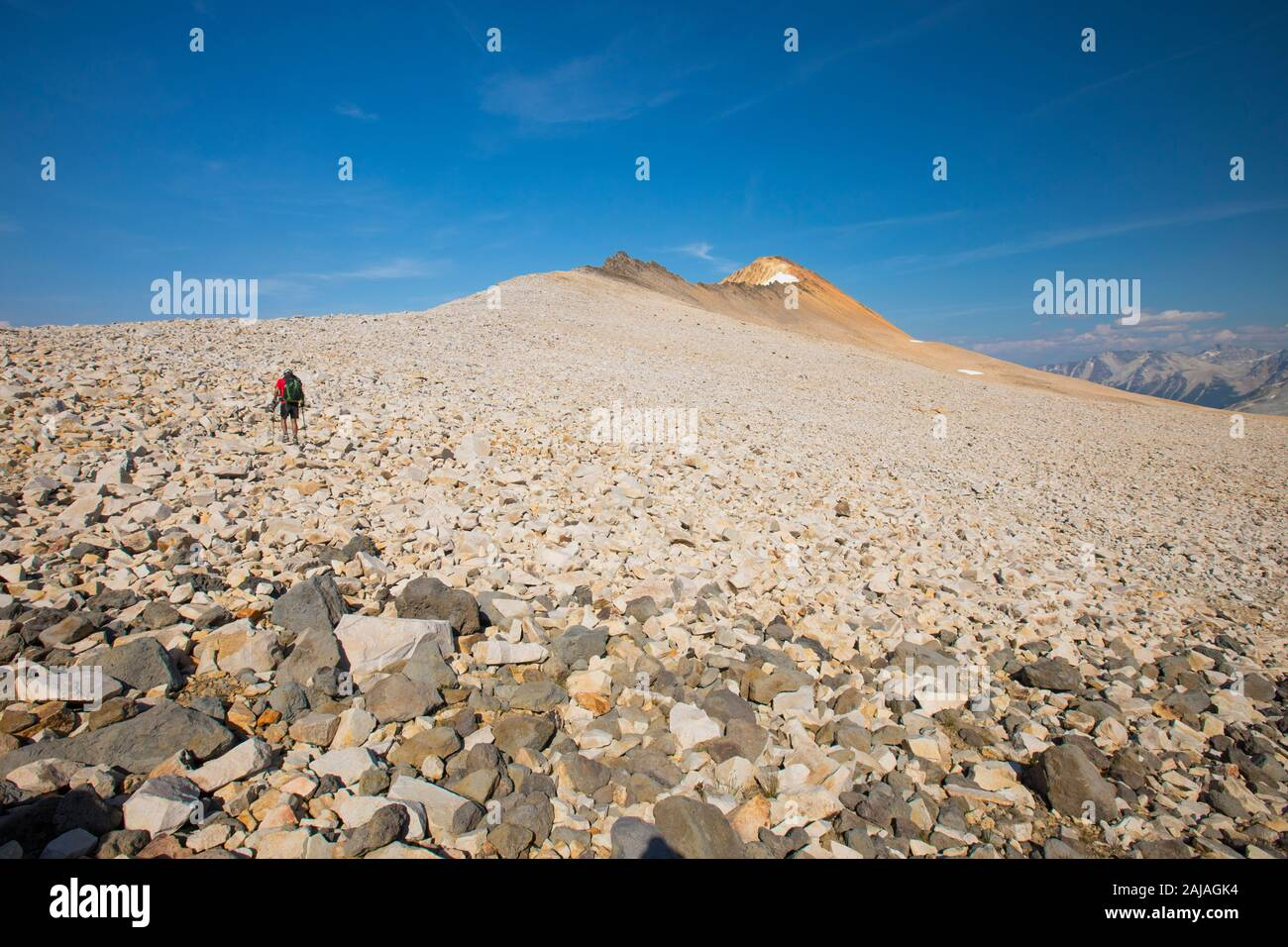 Backpacker crosses boulder field en route to Orchre Mountain. Stock Photo