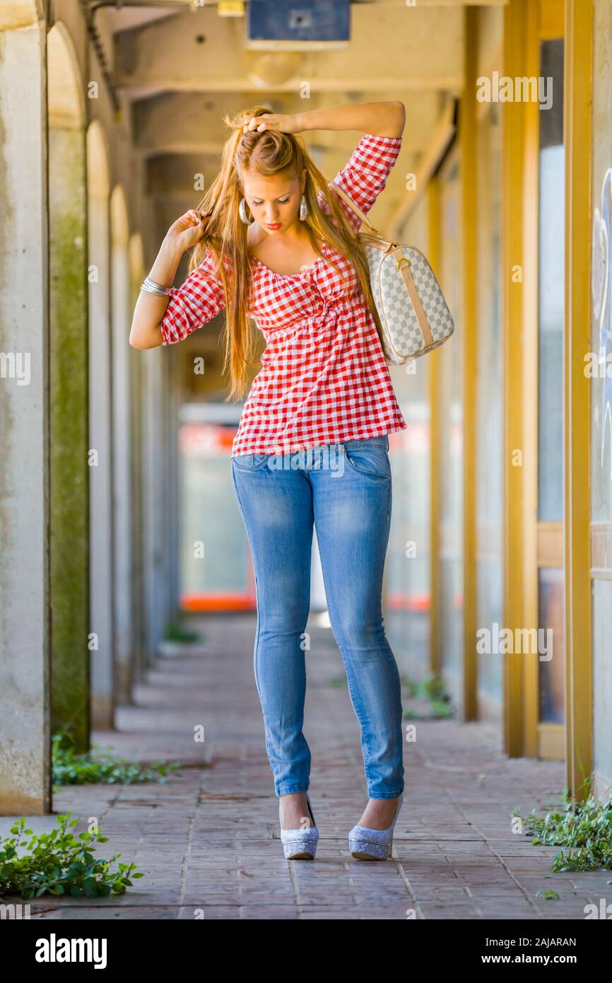 Standing fixing her hair serious looking down unaware Stock Photo