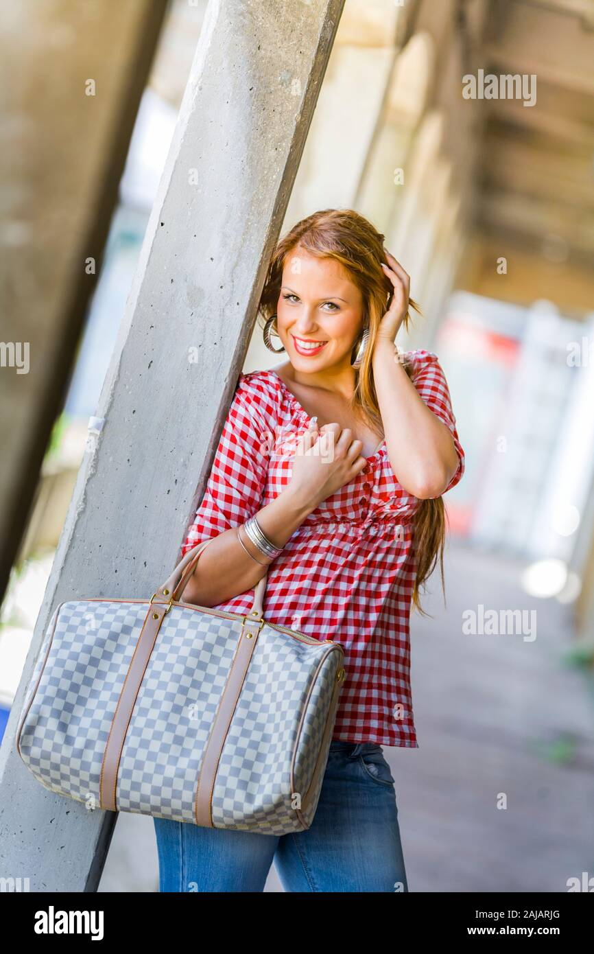 Standing leaning inclined on concrete post hand touching touch hair head giggling Stock Photo